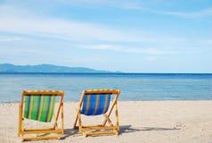 在白色沙子海滩的海滩睡椅与透明的海 免版税库存图片