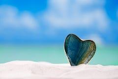 在白色沙子海滩的绿色玻璃心脏, 库存图片