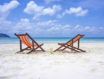 在白色沙子的两张海滩睡椅在蓝色海前靠岸 库存图片