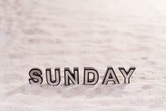 在白色沙子的星期天词 库存照片