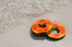 在白色沙子的番木瓜切片和水晶浇灌 库存照片