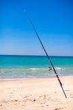 在白色沙子的钓鱼竿在热带海滩 免版税库存照片