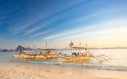在白色沙滩的传统菲律宾小船在口岸巴顿,巴拉望岛,菲律宾的日落 图库摄影