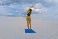 在白色沙漠沙子的瑜伽姿势 免版税库存照片