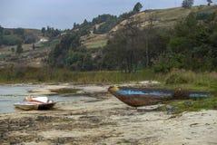 在白色海滩的被放弃的老小船 免版税库存图片