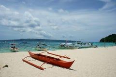 在白色海滩的小船 免版税图库摄影