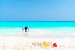 在白色海滩的沙堡与塑料哄骗玩具和家庭在海背景中 库存图片