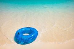 在白色海滩的蓝色救生圈 图库摄影