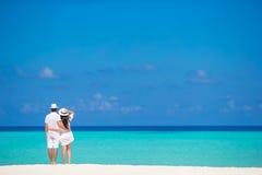 在白色海滩的年轻愉快的夫妇在夏天 库存照片