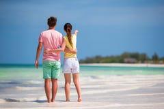 在白色海滩的年轻愉快的夫妇热带假期 免版税库存照片