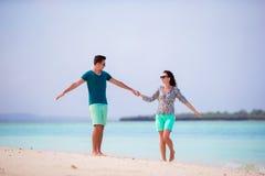 在白色海滩的年轻愉快的夫妇热带假期 库存照片