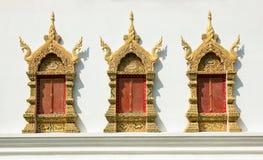 在白色混凝土墙上的金黄窗架在寺庙 免版税库存图片