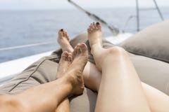 在白色游艇甲板的男人和妇女腿 图库摄影