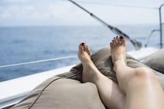 在白色游艇甲板的男人和妇女腿 免版税库存图片