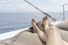 在白色游艇甲板的男人和妇女腿 库存图片