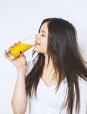 在白色演播室隔绝的可爱的白种人微笑的妇女画象射击了饮用的橙汁面孔皮肤 相当纵向 免版税图库摄影