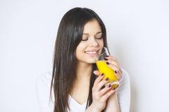 在白色演播室隔绝的可爱的白种人微笑的妇女画象射击了饮用的橙汁面孔皮肤 相当纵向 库存图片