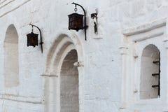 在白色灰泥砖墙的伪造的铁街灯有曲拱窗口的 图库摄影