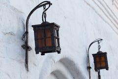 在白色灰泥砖墙选择聚焦特写镜头的伪造的铁街灯 库存照片