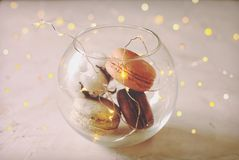在白色灰色具体织地不很细背景的传统法国杏仁焦糖巧克力蔓越桔macarons点心饼干盛肉盘 库存照片