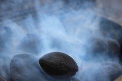 在白色烟的黑煤炭 图库摄影