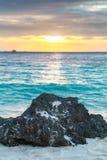 在白色热带海滩日落海的大黑石头 免版税图库摄影