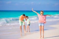 在白色热带海滩的爸爸家庭和孩子获得很多乐趣 免版税图库摄影