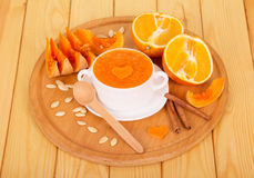 在白色焙盘、切的桔子和香草的南瓜纯汁浓汤在轻的木板条黏附 库存照片