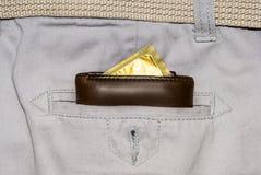 在白色牛仔裤的一个口袋的钱包有金避孕套的 库存照片