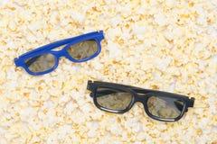在白色玉米花背景有两副眼镜观看的3D电影 免版税库存照片