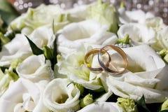 在白色玫瑰的婚戒 图库摄影