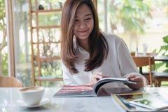 在白色现代咖啡馆的亚洲妇女阅读书 库存照片