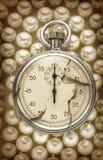 在白色珍珠的破裂的秒表 免版税库存照片