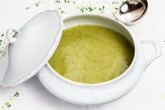 在白色瓷焙盘的蔬菜汤与银色杓子 免版税库存照片