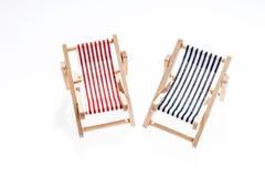 在白色的两张空的海滩睡椅 免版税库存图片