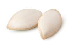 在白色的两粒盐味的南瓜籽 库存照片