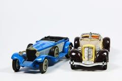 在白色的两辆玩具葡萄酒模型汽车 库存照片