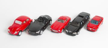 在白色的五辆减速火箭的红色和黑玩具汽车,男孩的玩具 免版税库存图片