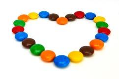 在白色的五颜六色的巧克力按钮 免版税库存图片