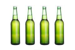 在白色的四个绿色啤酒瓶 免版税库存图片