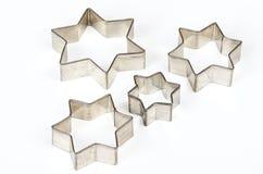 在白色的四星形状的圣诞节曲奇饼切削刀 免版税库存图片