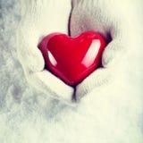 在白色的女性手编织了有光滑的红色心脏的手套在雪冬天背景 爱和圣华伦泰舒适概念 免版税库存图片