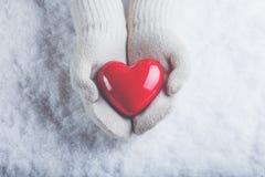 在白色的女性手编织了有光滑的红色心脏的手套在雪背景 爱和圣华伦泰概念 免版税图库摄影