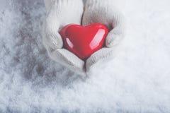 在白色的女性手编织了有光滑的红色心脏的手套在雪背景 爱和圣华伦泰概念 库存图片