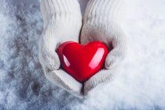 在白色的女性手编织了有光滑的红色心脏的手套在雪背景 爱和圣华伦泰概念 库存照片