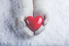 在白色的女性手编织了有光滑的红色心脏的手套在雪背景 爱和圣华伦泰概念 图库摄影