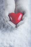 在白色的女性手编织了有光滑的红色心脏的手套在雪背景 爱和圣华伦泰概念 免版税库存图片