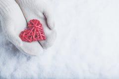 在白色的女性手编织了有纠缠的葡萄酒浪漫红色心脏的手套在雪背景 爱和圣华伦泰概念 图库摄影