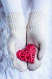 在白色的女性手编织了有纠缠的葡萄酒浪漫红色心脏的手套在雪背景 爱和圣华伦泰概念 免版税库存照片