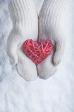 在白色的女性手编织了有纠缠的葡萄酒浪漫红色心脏的手套在雪背景 爱和圣华伦泰概念 库存图片